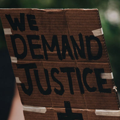 """Stock image from UNSPLASH of person holding up a placard saying """"Wed demand justice + change"""""""