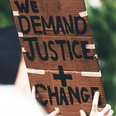 """Stock image from UNSPLASH of person holding placard saying """"Demand justice + change"""""""