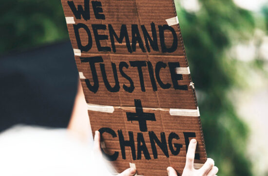"Stock image from UNSPLASH of person holding placard saying ""Demand justice + change"""
