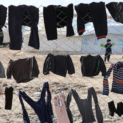 Image of clothes drying on fence in North East Syrian camp, by REUTERS/Goran Tomasevic