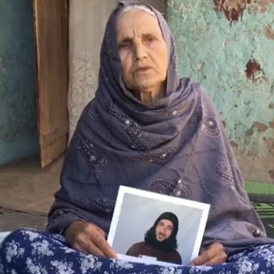 Twitter image of Asadullah Haroon Gul's mother holding up pictures of him while he is locked up in Guantanamo.